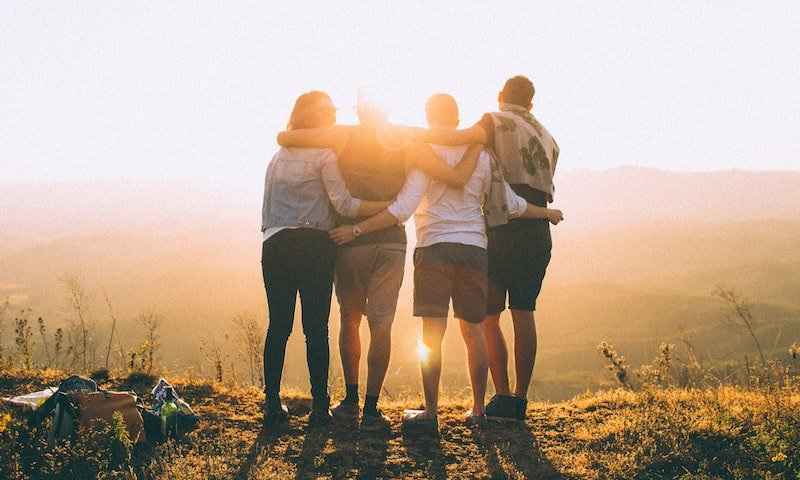 group of friends embracing on a mountain top